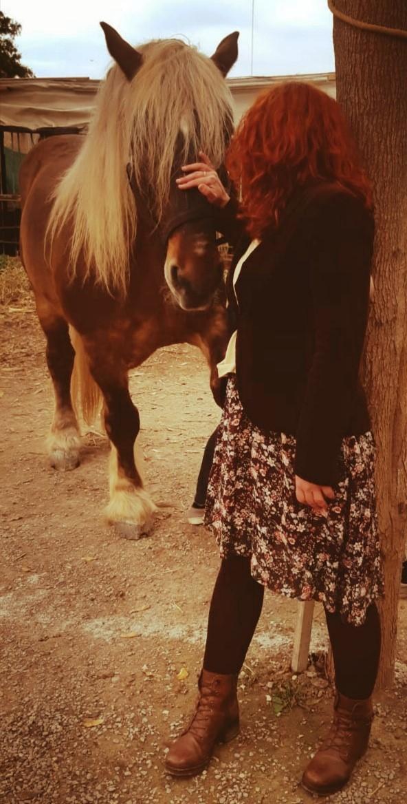 Luz Ros, mujer acariciando a un caballo en la Barraca de Toni Montoliu